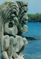 Carved wooden temple gods with Honaunau Bay in the background